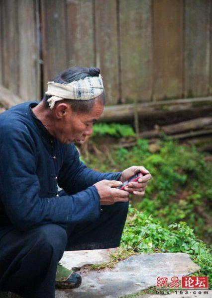 Sambil menunggu tukang cukur mengasah sabit, pelanggan ini sibuk berkomunikasi dengan temannya menggunakan hp.
