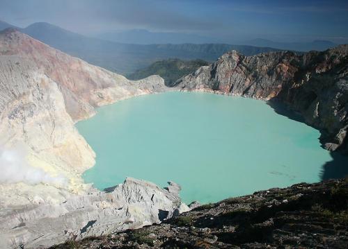 Danau Kawah Ijen dilihat dari bibir Kawah dengan latar belakang air danau yang tenang berwarna hijau toksa.