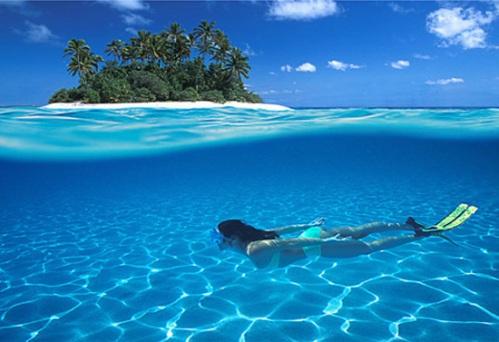 Seorang turis wanita tengah menyelam dalam beningnya air laut