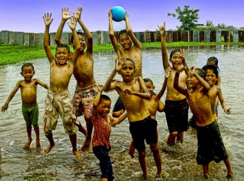 Kubangan air banjir menjadi sarana anak-anak bermain dengan gembira. Mereka tertawa, bercanda dan