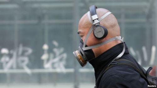 Seorang pria China harus mengenakan masker akibat udara kotor dan kabut asap yang menyelimuti Beijing. Polusi udara bisa terjadi karena asap kendaraan, asap dari cerobong pabrik, dan kabut asap dampak pembakaran hutan.