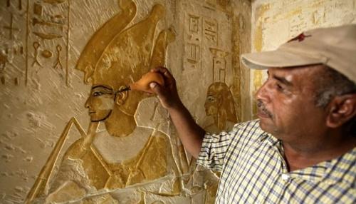 Seorang pekerja sedang membersihkan debu yang menempel pada relief di enam makam kuno yang baru dibuka untuk umum di New Kingdom Cemetery, Saqqara, Mesir.