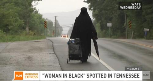 Wanita berpakaian hitam berjalan lamban seakan menuju alamat tak jelas yang dicarinya.
