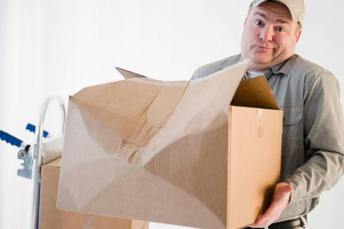 Petugas paket DHL dengan sabar mencari tumpukan kardus yang berisi abu jenazah ayah N