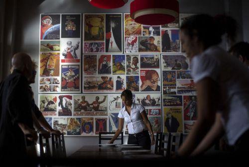 Seorang pelayan restoran menyajikan pesanan makanan dengan latar belakang berbagai propaganda reproduksi poster propaganda Soviet menggantung di dinding di restoran Nazdarovie baru sebagai pelayan mempersiapkan meja untuk latihan pra-peluncuran di Havana, Kuba.
