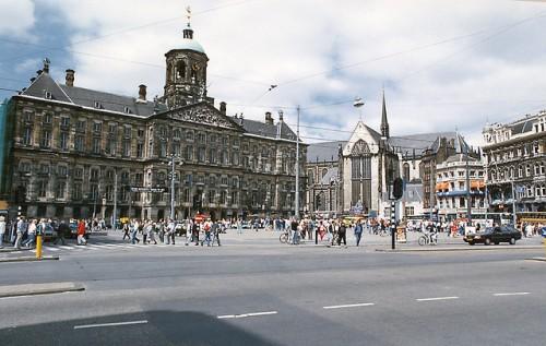 Turis lokal dan asing menyempatkan diri membaur di kawasan Dam Square menikmati cuaca cerah saat musim panas di Amsterdam.