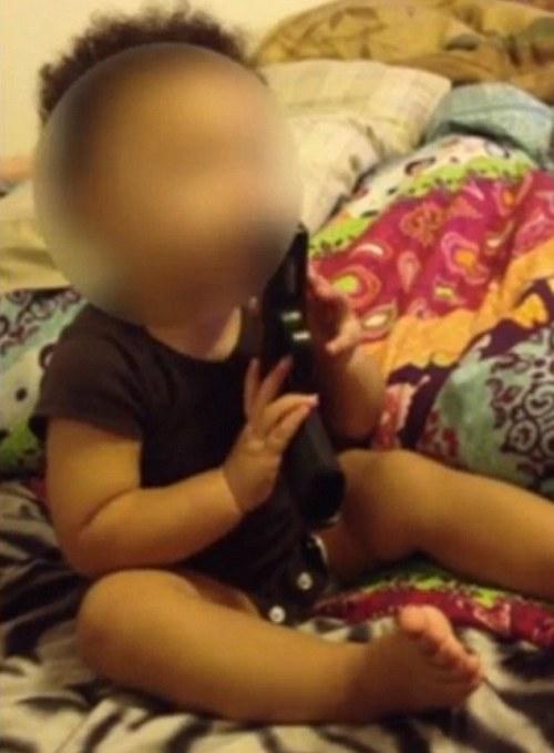 Bayi memegang pistol sedang diarahkan Michael Barnes untuk berkata dor.