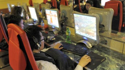 Pengunjung warnet di Beijing sedang main games on lines dengan lawan mainnya di Amerika Serikat. Maraknya penggunaan internet, warung internet selalu menyediakan permainan game.