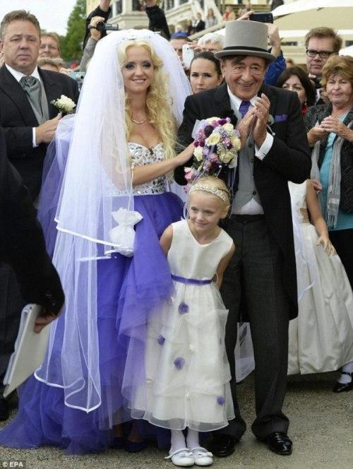 Pasangan pengantin sepuh dan muda ceria menerima ucapan selamat dari para tamu.