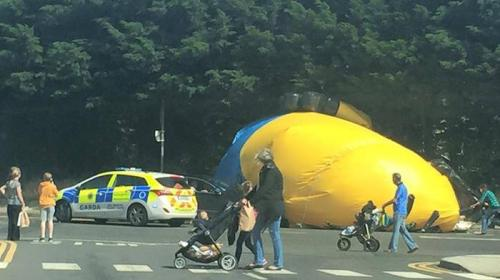 Pengunjung menyaksikan boneka raksasa minion yang lepas dan jatuh di jalan raya.