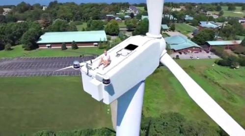 Subjective kamera pesawat nirawak merekam ada pria sedang duduk manis di puncak turbin angin.