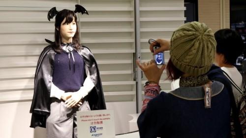 Robot humanoid Chihira Junko ( L ) , mengenakan kostum Halloween , menyapa pelanggan yang asyik memotretnya.