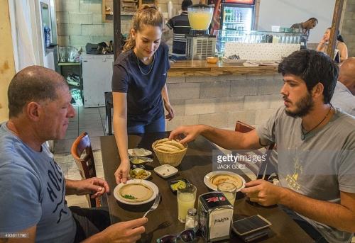 Pelanggan dilayani piring hummus di Hummus Bar pemilik , Kobi Tzafrir , di kota Israel tengah Kfar Vitkin , pada 21 Oktober 2015 yang menawarkan diskon 50 persen.
