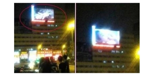 Screenshot via Sina Weibo Video porno yang diputar di billboard digital dekat stasiun kereta Jilin City, China.