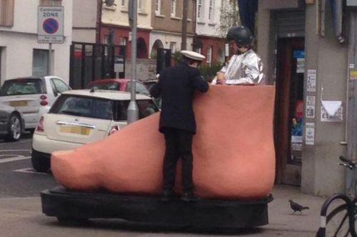 Foto polisi menilang pria yang mengendarai kaki raksasa di jalan Kota London, Inggris (Foto: Kepolisian Wandsworth/ Mirror)