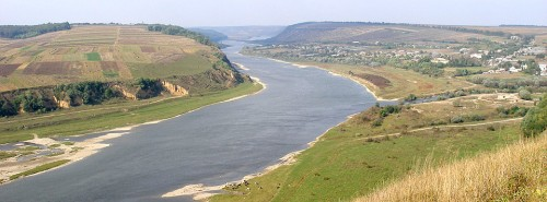 Sungai Dniester Ukrania saat musim panas dengan tumbuhnya rumput liar di sepanjang aliran sungai.