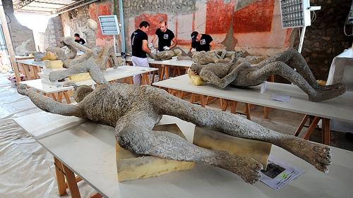 Pekerja menangani para korban membatu akibat letusan Gunung Vesuvius pada tahun 79 sebelum Masehi. Aktivitas itu sebagai bagian dari pekerjaan besar merestorasi dan mempelajari 86 gips di laboratorium Pompeii Archaeological Site, Rabu (20/5), di Pompeii, Italia selatan. AFP/MARIO LAPORTA.