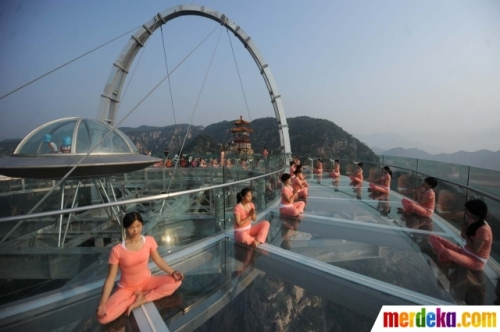 Sejumlah wanita berlatih yoga di atas panggung kaca yang berada di pinggir tebing di Beijing, China, Senin (20/6). Kegiatan ini dilakukan untuk menyambut perayaan Hari Yoga Internasional pada 21 Juni.