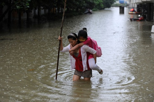 Ibu tengah menggendong anaknya melintasi genangan air kota Wuhan.