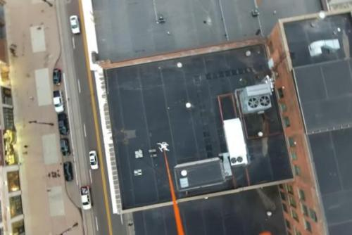 Sebuah pesawat tak berawak mengangkat sebuah pesawat tak berawak jatuh dari atap Detroit. Screenshot: Random Axe / YouTube