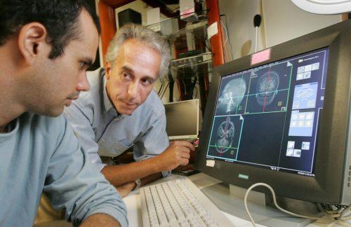 Reed Saxon / AP Dr. Marco Iacoboni (kanan) dan asisten riset Jonas Kaplan melihat scan MRI dari otak relawan dalam penelitian mereka tentang bagaimana pemilih berpikir.