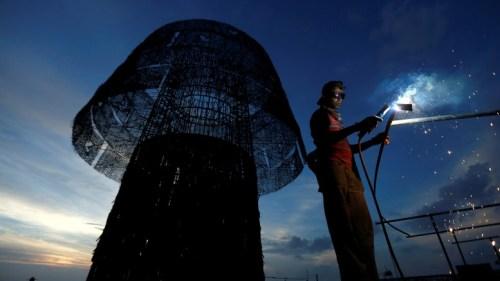 Seorang pekerja konstruksi Sri Lanka Kementerian Pelabuhan dan Pengiriman bekerja pada sebuah pohon Natal besar dalam upaya untuk membangun tertinggi di dunia ...